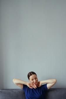 リビングルームのソファで休んで腕を伸ばしている女性