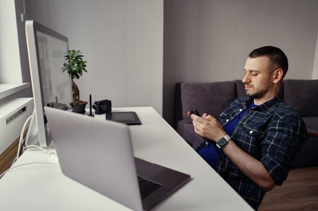 ホームオフィスで一時停止している間手でスマートフォンを保持している若い男
