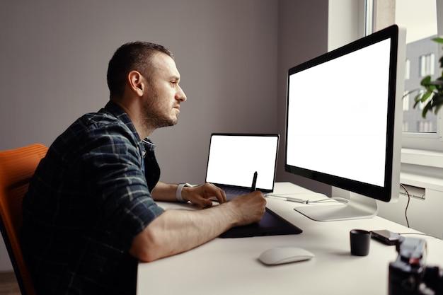 若い男がインタラクティブなペンのディスプレイとコンピューターでの作業