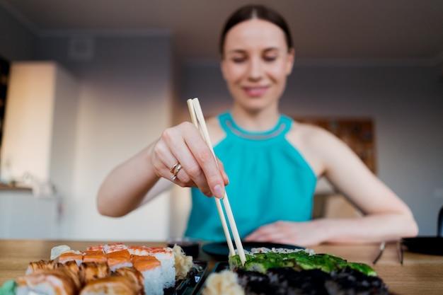 Счастливая женщина ест вкусные суши