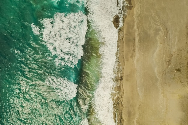 Аэрофотоснимок песка, встреча морской воды и волн
