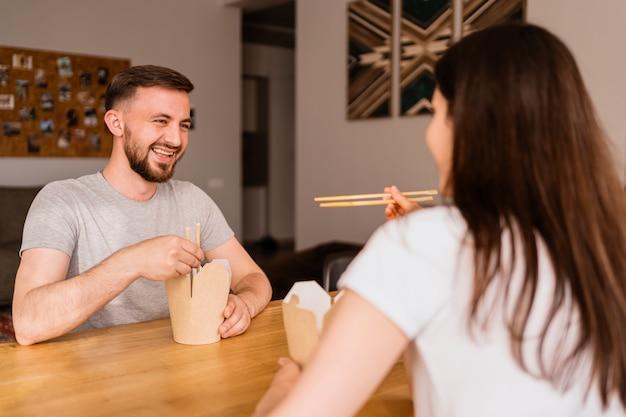 家で一緒に昼食を食べて笑顔の男と女