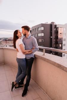 Мужчина и женщина на балконе на закате в городе