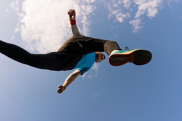 スポーツマンが走って空に飛び込む