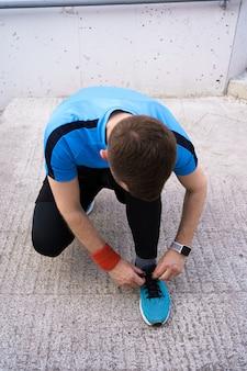 コンクリート背景に彼のスポーツの靴を結ぶ男