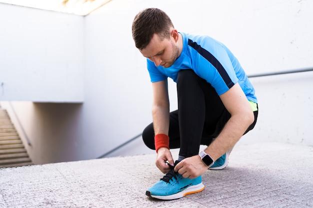 Человек, связывая его спортивную обувь на бетонном фоне