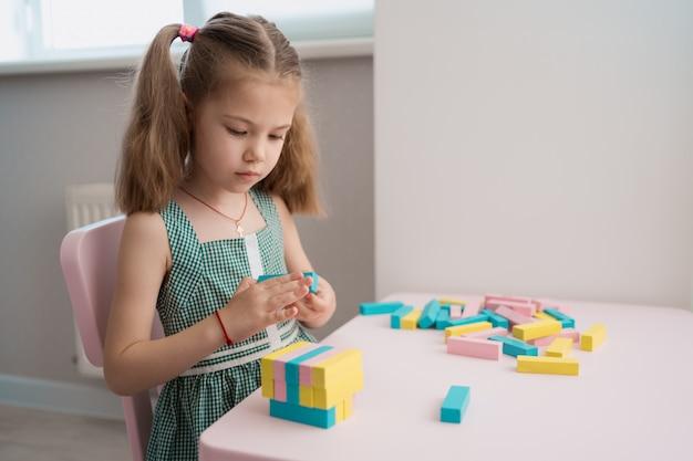 Красивая кавказская девушка играет с деревянными разноцветными блоками