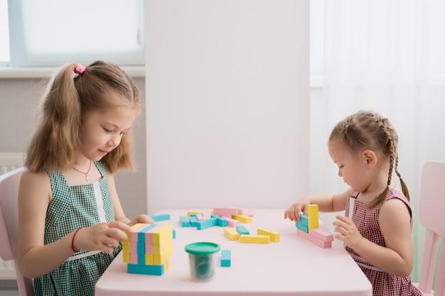 Красивые кавказские девушки играют с деревянными разноцветными блоками
