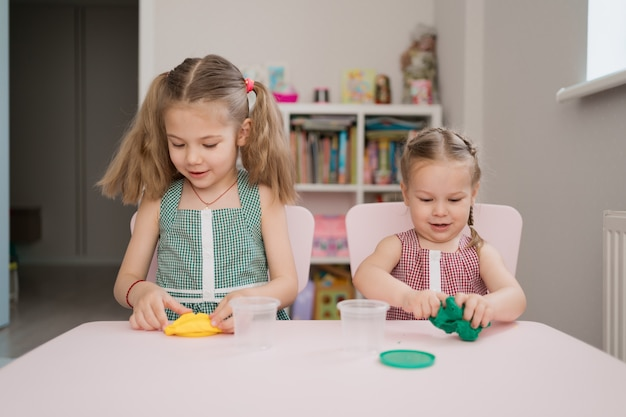 ピンクのテーブルに粘土から成形かわいい女の子