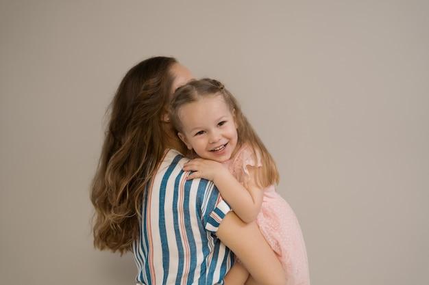 Портрет матери и дочери на бежевом фоне
