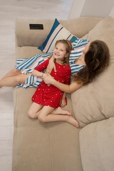 Портрет матери и дочери, лежа на диване