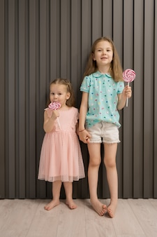Милые маленькие девочки с леденцом на палочке на сером фоне