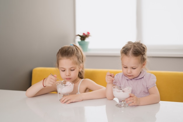 テーブルでアイスクリームを食べる女の子
