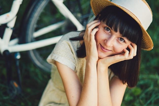 Молодая женщина на фоне природы с велосипедом
