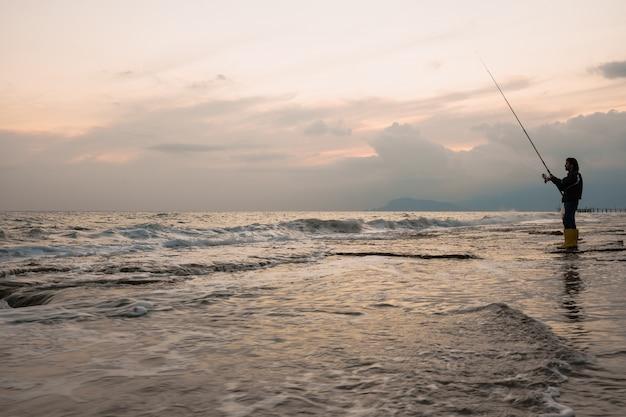 男は海岸で釣り