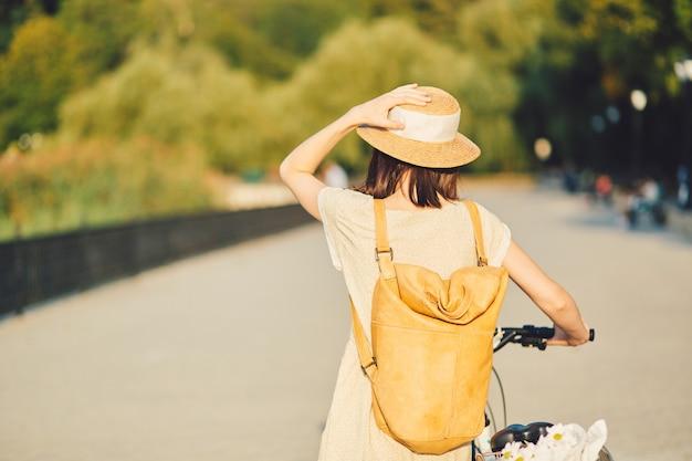 自転車に乗って帽子の魅力的な若いブルネットの屋外のポートレート。