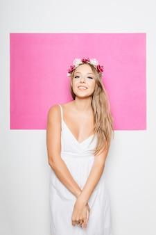 髪を笑顔で花と白い綿のドレスを着た女性