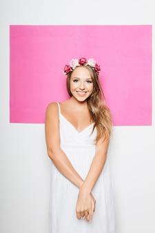 Женщина в белом хлопчатобумажном платье с цветами в волосах улыбается