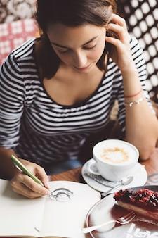ノートにコーヒーのカップを描いている女の子