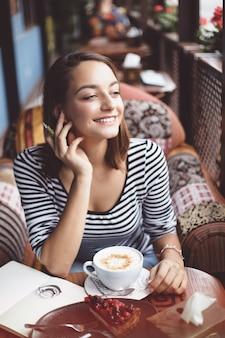 Молодая женщина сидит крытый в городских кафе