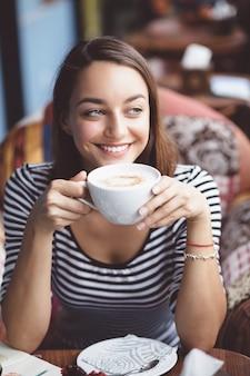 Молодая женщина пьет кофе в городских кафе