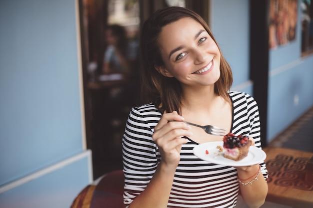 Молодая женщина ест клубничный чизкейк