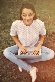 緑の芝生に座ってラップトップを持つ若い女