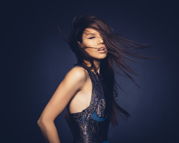 スタジオでポーズをとって髪を飛んで魅力的な女の子