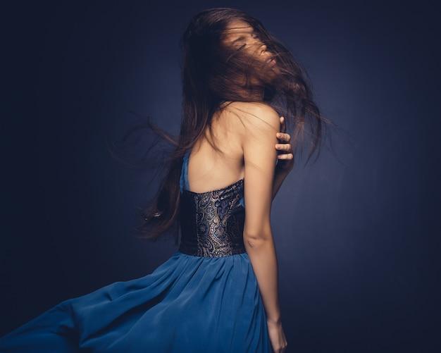 Привлекательная девушка с развевающимися волосами позирует в студии