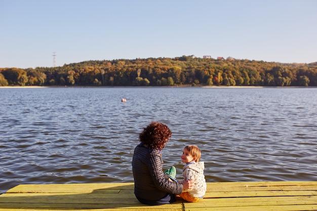 ママと息子が湖で休んで