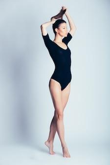 スタジオでポーズをとる若くて美しいダンサー