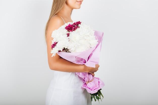 花の束を保持しているクローズアップの繊細な女性の手