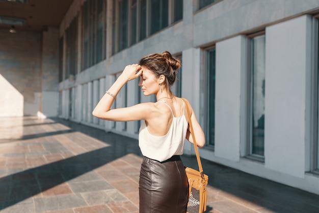 Изысканная молодая женщина в кожаной юбке и шелковой блузке думает, как решить ситуацию.