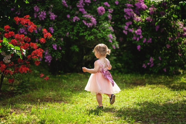 Маленькая девочка со светлыми волосами в розовом платье бежит в цветущем парке