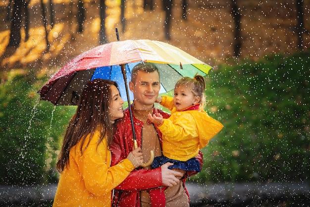 Молодая семья наслаждается дождем. прогулка по осеннему солнечному парку.