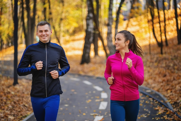女と男のジョギングや丘の上の秋の間に公園で実行