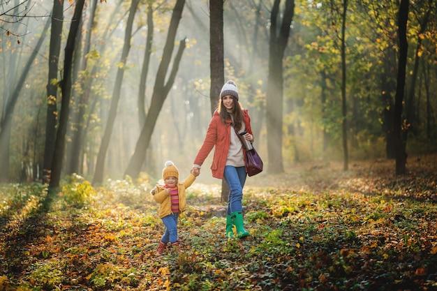 秋の自然の森を歩く幼児の娘を持つ若い母親。