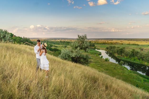 Молодая пара счастлива и стоит на лугу вечером в летний сезон