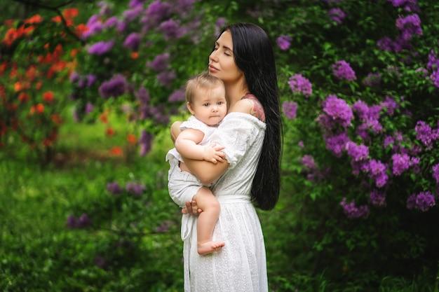 Милая молодая мать, держа ее ребенка в цветущем саду