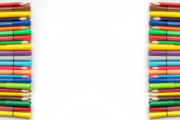 色鉛筆の境界線とフェルトペンホワイトペーパーの背景に、スペースをコピーします。学校に戻る事務用品。上面図。