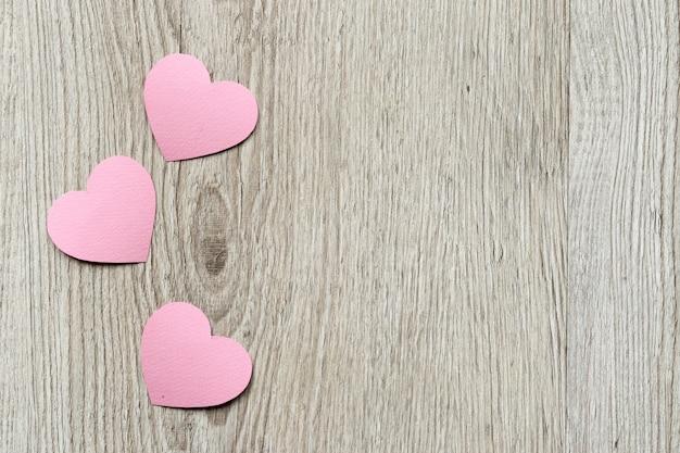 バレンタインデーカードの背景、紙で作られたピンクのかわいいハート。紙のカットテクニックで心を持つ木製の背景。ロマンチックなバレンタインの日。