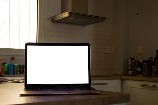キッチンに白い画面のラップトップ