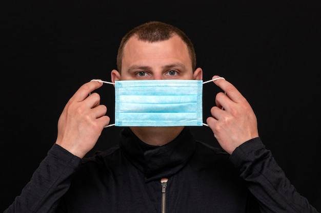 男性が顔に医療用マスクを装着し、マスクの着用方法の指示