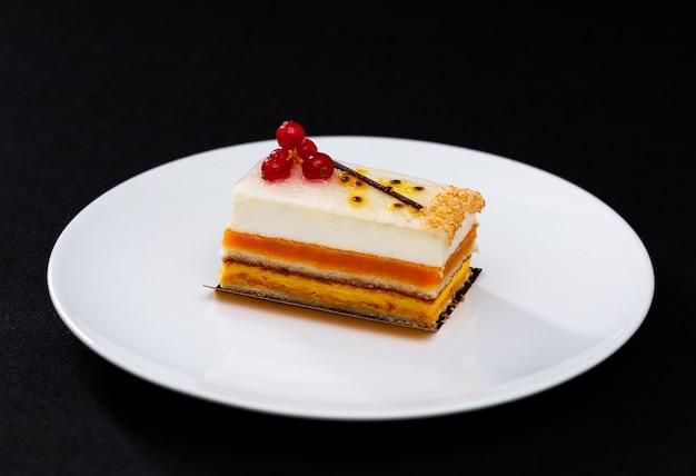 デザートサービング、白い皿に白いクリームと赤スグリの多層美しいケーキ