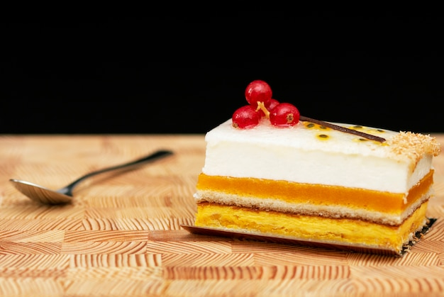 木製の背景、小さなスプーンにエアクリームと赤スグリの多層ケーキ