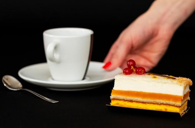 風通しの良い白クリームと赤スグリの入った多層ケーキ、口の水まきデザート、小さなスプーンの白いカップ