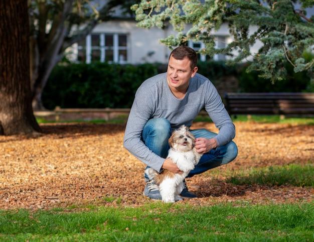 シーズーの子犬の屋外で遊ん男、公園で犬の訓練