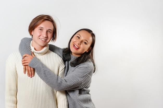 Портрет двух счастливых молодых людей в теплые кофты - брат и сестра.