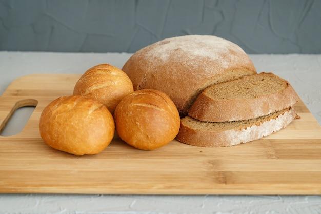 Ржаной хлеб и булочки на деревянной доске на сером
