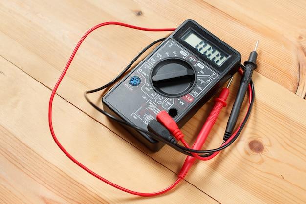 デジタルマルチメータと木製のテーブルの配線。回路および電気での作業のための技術者の特別なツール。技術者はワークショップでデジタル機器を使用して小切手修理装置